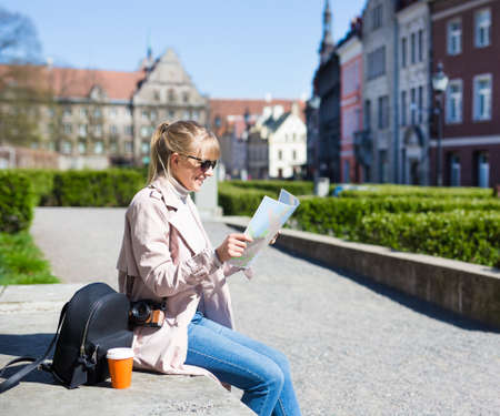 summer vacation and travel concept - happy woman in sunglasses with map, backpack and camera in old town of Tallinn, Estonia