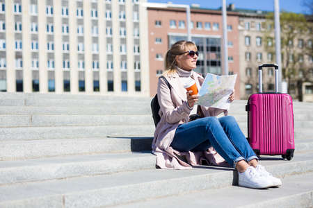 summer vacation, tourism and travel concept - young female tourist with map and suitcase - copy space over stairs 스톡 콘텐츠 - 124962484