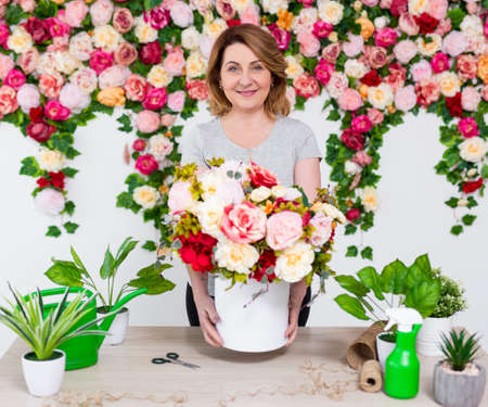 portrait of smiling mature woman florist working in beautiful flower shop Banco de Imagens - 124962607