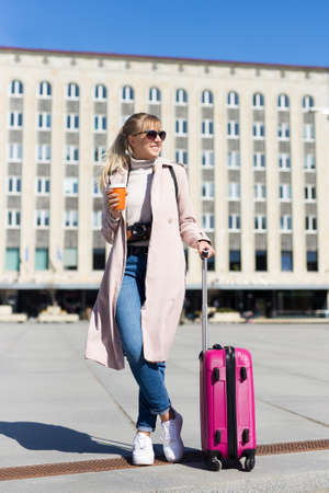 summer vacation, tourism and travel concept - young woman with suitcase