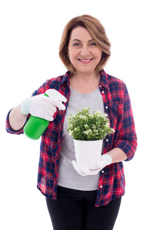 portrait of middle aged woman gardener with potted plant and watering spray bottle isolated on white background Stockfoto