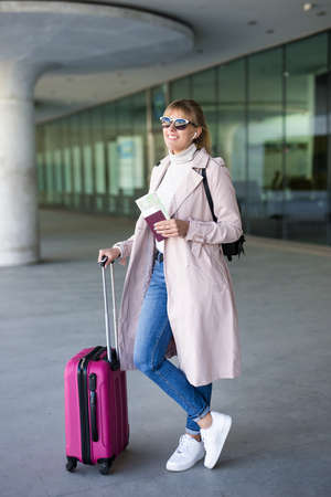 tourism and travel concept - young female tourist with suitcase and passport waiting boarding in airport or bus station