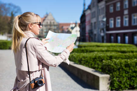 summer vacation and travel concept - back view of female tourist in sunglasses with map and camera walking in old town