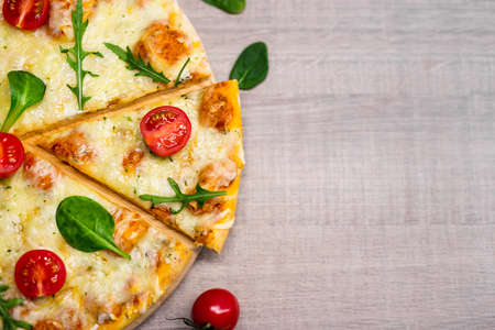 close up top view of pizza with tomatoes and herbs over wooden table background 스톡 콘텐츠