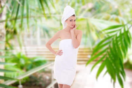 beauty and spa concept - portrait of young beautiful woman wrapped in towel over summer background