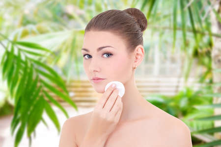 portrait of young beautiful woman cleaning her face skin by cotton pad over summer background Stock Photo