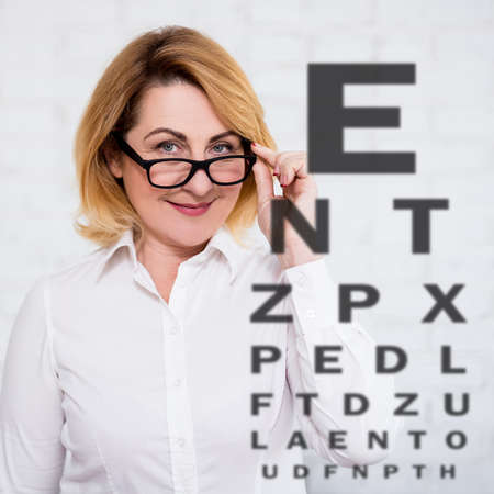 mature woman in eyeglasses and eyevision test chart over white wall background