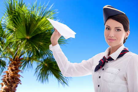 summer, vacation and travel concept - stewardess with paper plane over blue sky background with palm tree