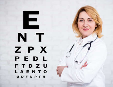 portrait of mature female doctor or nurse posing over white wall with eye test chart Banco de Imagens - 124962662