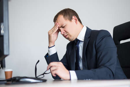 business and depression concept - portrait of stressed businessman sitting in modern office Imagens
