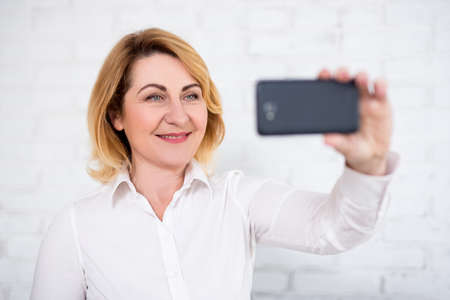 portrait of cheerful mature business woman taking selfie with smart phone over white brick wall