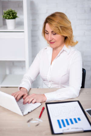 mature business woman with laptop in modern office