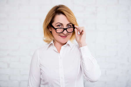 portrait of cheerful mature business woman in eyeglasses posing over white brick wall