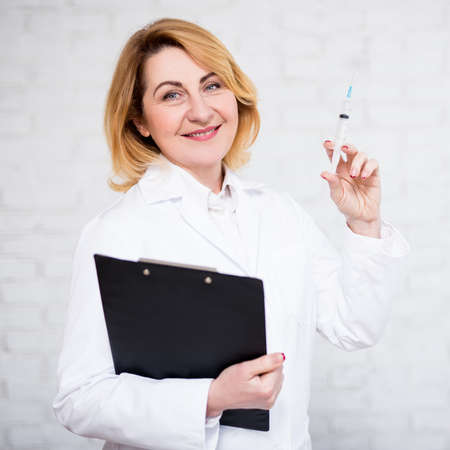health care, vaccination and cosmetology concept - mature female doctor or nurse with syringe over white brick wall Banco de Imagens