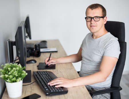 portrait of young handsome male photographer editing images with computer in modern office or at home 写真素材