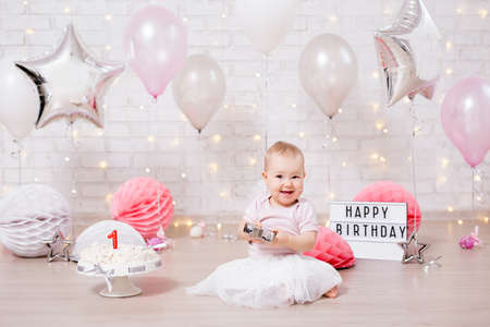 crashed party concept - happy baby girl and smashed cake over brick wall with lights and balloons