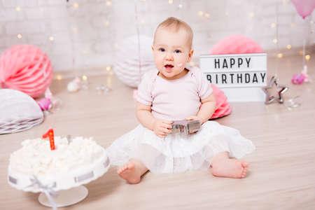 concept de premier anniversaire - portrait d'une jolie petite fille et d'un gâteau brisé avec des décorations d'anniversaire
