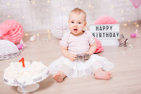 first birthday concept - portrait of cute baby girl and smashed cake with birthday decorations