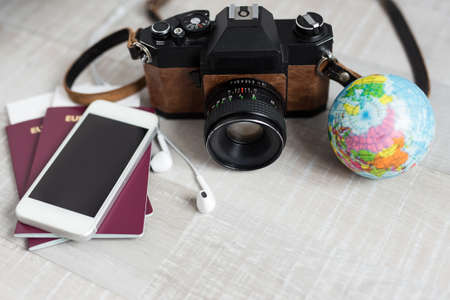 travel and vacation concept - close up of passports, camera, smart phone and little globe over wooden table background