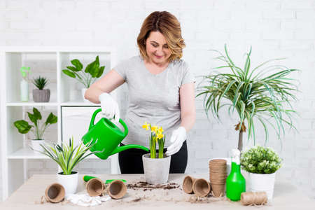 portrait of happy mature woman planting and watering spring flowers at home