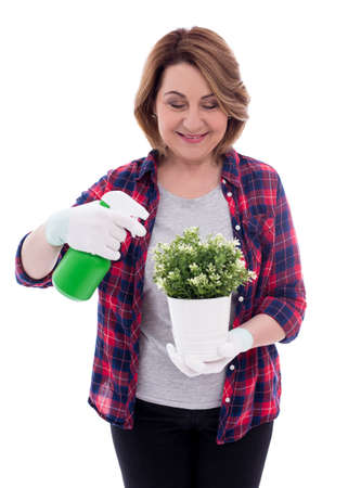 portrait of smiling mature woman gardener with potted plant and watering spray bottle isolated on white background