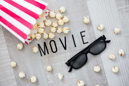 cinema concept - close up of 3d glasses and popcorn with movie word