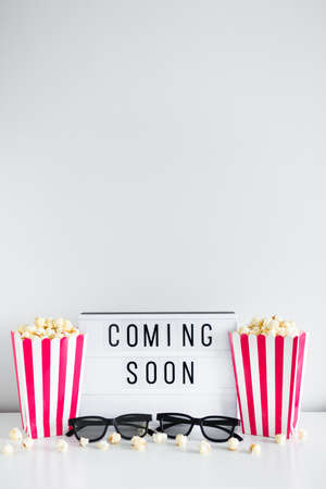 cinema concept - striped boxes with popcorn, 3d glasses, light box with coming soon text and copy space over white background