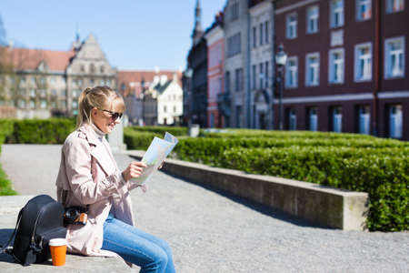 summer and travel concept - woman in sunglasses with map, backpack and camera in old town of Tallinn, Estonia, Europe Stock Photo