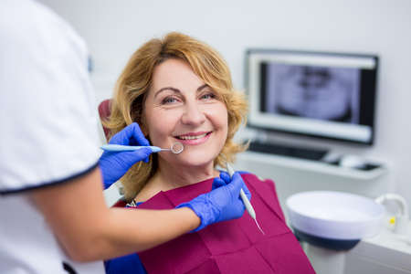 portrait of cheerful mature woman patient in dental clinic
