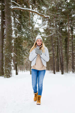 full length portrait of young blond woman walking in winter forest with thermo cup of coffee