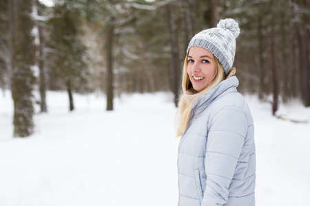 portrait of young beautiful blond woman in winter forest Banco de Imagens