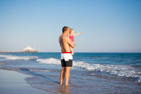 summer vacation and travel concept - happy father walking with little daughter at the beach