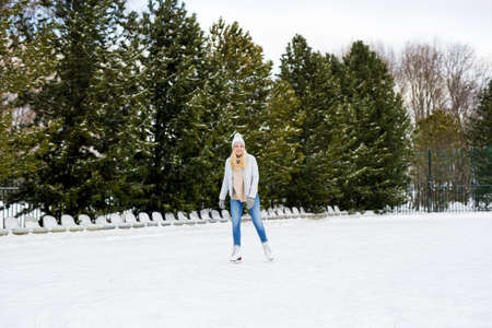 full length portrait of happy young blond woman skating at outdoor rink Stockfoto