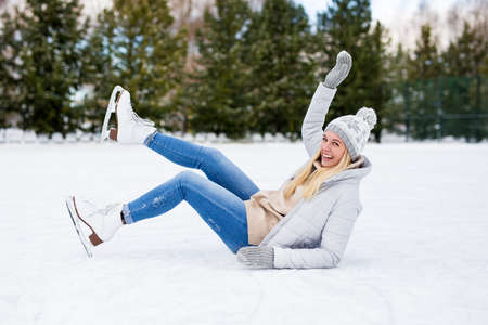 funny girl falling down while ice skating at winter rink