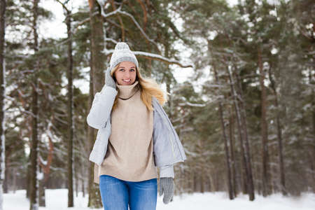 portrait of young beautiful blond woman posing in winter forest