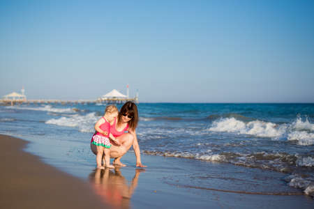 summer and travel concept - portrait of happy mother with her little daughter at the beach Zdjęcie Seryjne