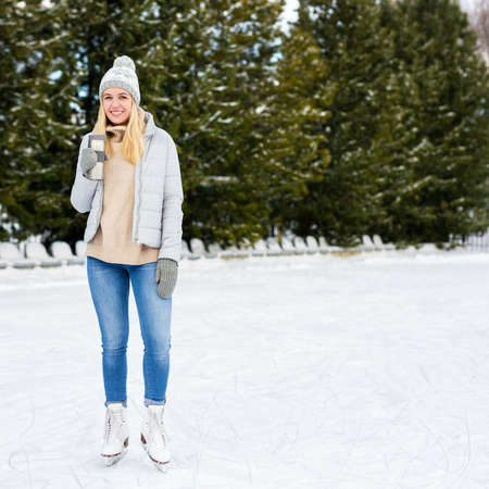 full length portrait of happy young woman ice skating and drinking coffee at rink in winter park Stockfoto