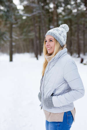 portrait of young beautiful blond woman walking in winter park or forest Banco de Imagens