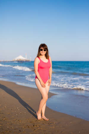summer and travel concept - young woman in pink swimsuit walking or posing at the beach Banco de Imagens