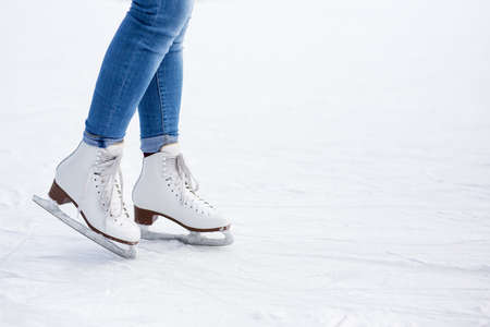 legs in white leather skates and copy space over white ice at rink Banque d'images - 130126909