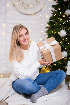 portrait of young blond woman sitting in living room with decorated Christmas tree and gift boxes