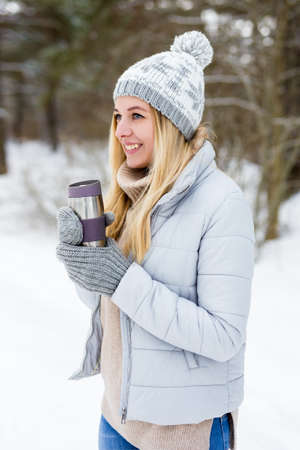 portrait of young beautiful blond woman with thermo cup of coffee in winter park or forest
