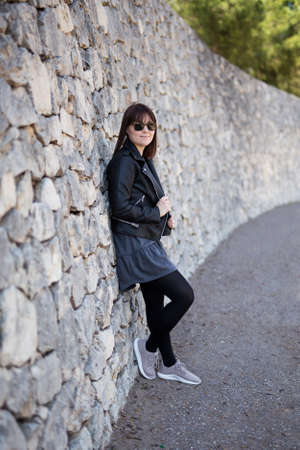 full length portrait of young woman in leather jacket and sunglasses posing over stone wall