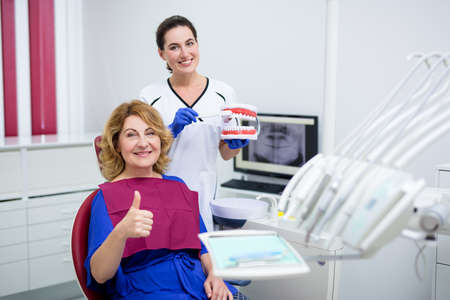 attractive female doctor with toothbrush and artificial jaws and mature woman patient