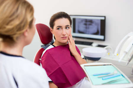 attractive woman with pain talking with doctor in modern dentist office