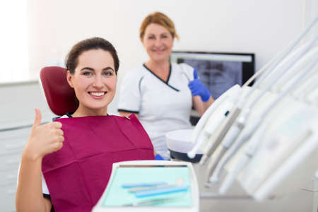 portrait of young smiling woman patient thumbs up at dental clinic