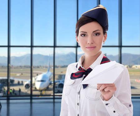 concepto de verano, vacaciones y viajes - azafata posando con avión de papel en el aeropuerto Foto de archivo