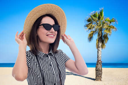 summer and travel concept - young beautiful woman in sunglasses and straw hat walking at the beach