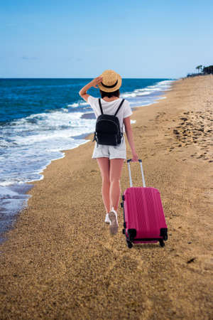 summer vacation and travel concept - back view of young woman tourist in straw hat with suitcase and backpack walking at sandy beach Banco de Imagens