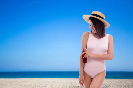 summer and travel concept - young woman in pink swimsuit and straw hat applying sunscreen spray at the beach with white sand - copy space over blue sky Фото со стока